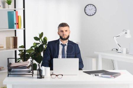 Photo pour Homme d'affaires regardant la caméra près des gadgets et des dossiers papier sur le premier plan flou dans le bureau - image libre de droit