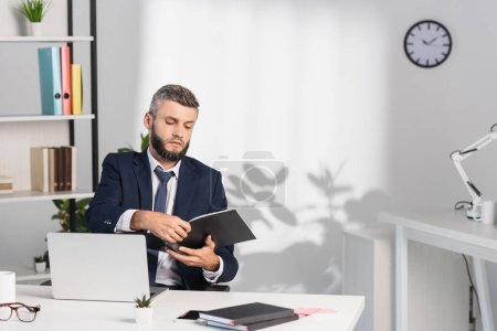 Businessman holding paper folder near gadgets and notebooks on blurred foreground