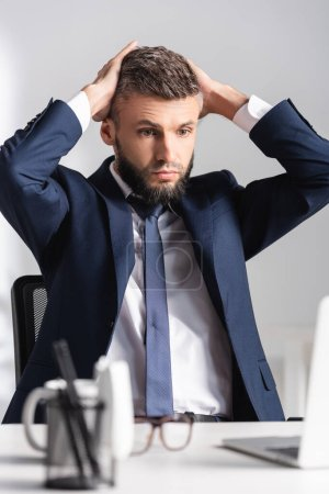 Tired businessman with hands near head looking at laptop on blurred foreground in office