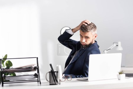 Photo for Exhausted businessman looking at laptop near stationery on blurred foreground in office - Royalty Free Image