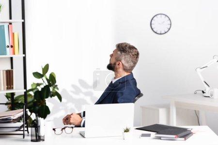 Geschäftsmann schaut weg, während er in der Nähe von Gadgets und Notizbüchern auf verschwommenem Vordergrund im Büro sitzt