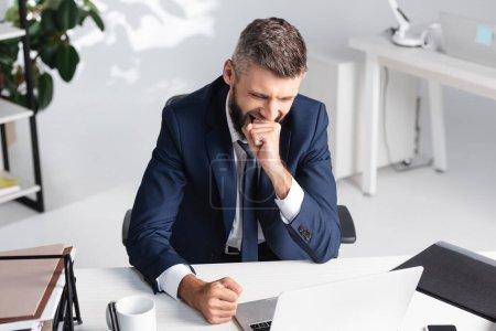 Photo pour Homme d'affaires bâillant tout en travaillant près de l'ordinateur portable et des papiers sur la table - image libre de droit