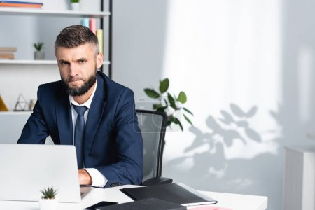 Photo for Bearded businessman looking at camera with laptop and paper folder on blurred foreground - Royalty Free Image