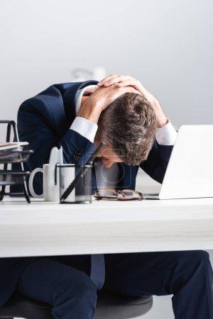 Foto de Hombre de negocios agotado tocando la cabeza cerca de la computadora portátil y artículos de papelería en primer plano borroso en la mesa - Imagen libre de derechos