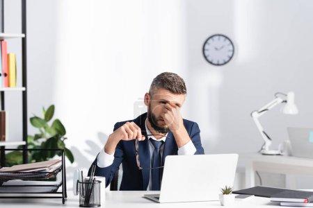 Foto de Empresario con la mano cerca de los ojos sosteniendo gafas al lado de la computadora portátil y artículos de papelería en primer plano borrosa en la mesa - Imagen libre de derechos