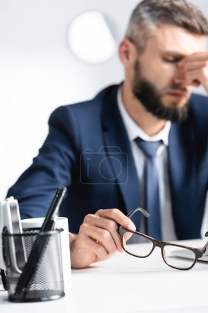 Photo for Eyeglasses in hand of overworked businessman near cup and stationery on table - Royalty Free Image