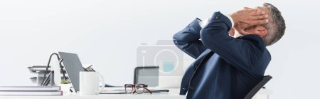 Tired businessman touching face near laptop and eyeglasses on blurred foreground in office, banner