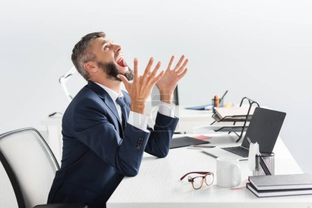 Photo for Irradiated businessman screaming while working near laptop and stationery in office - Royalty Free Image