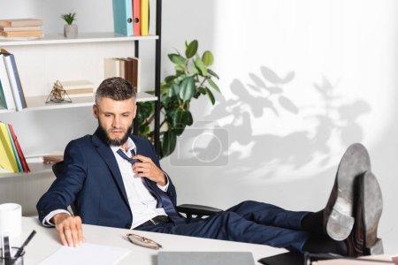 Photo pour Homme d'affaires touchant cravate tout en regardant les papiers près de l'ordinateur portable sur le premier plan flou dans le bureau - image libre de droit