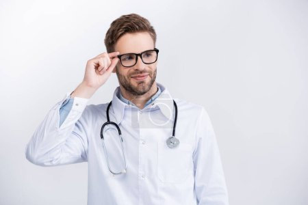 Photo for Smiling doctor with stethoscope holding eyeglasses frame, while looking away isolated on white - Royalty Free Image