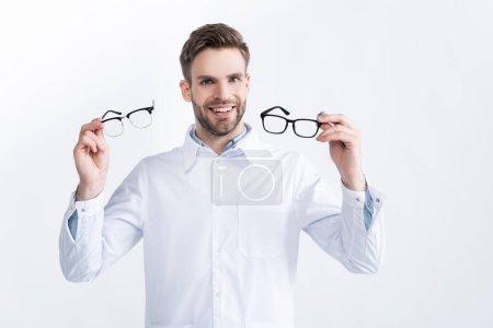 Photo pour Vue de face de l'ophtalmologiste souriant montrant une paire de lunettes, tout en regardant la caméra isolée sur blanc - image libre de droit