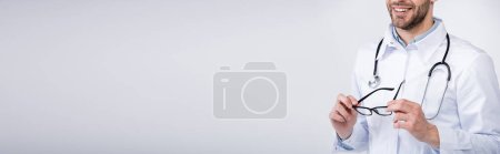 Cropped view of smiling doctor with stethoscope holding eyeglasses on grey background, banner