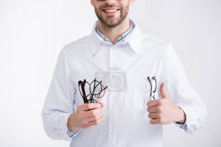 Cropped view of smiling doctor with thumb up, holding several eyeglasses isolated on white