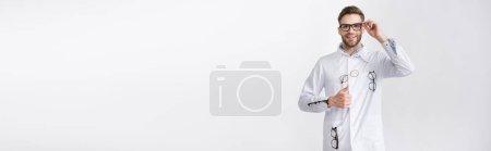 Photo pour Vue de face de l'ophtalmologiste heureux avec le pouce levé, vêtu d'un manteau blanc avec des paires de lunettes suspendues isolées sur blanc, bannière - image libre de droit