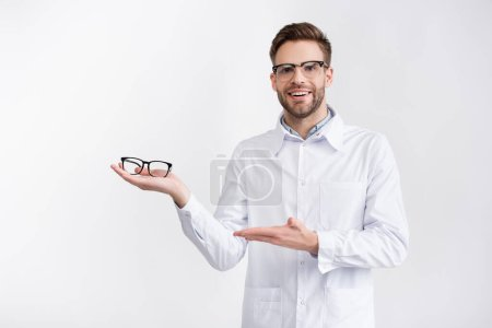 Front view of happy doctor holding and pointing with hand at eyeglasses on palm, while looking at camera isolated on white