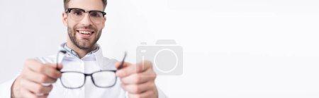 Photo pour Ophtalmologiste souriant mettre des lunettes isolées sur blanc sur le premier plan flou, bannière - image libre de droit