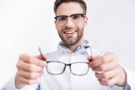 Photo pour Ophtalmologiste souriant mettre des lunettes isolées sur blanc sur le premier plan flou - image libre de droit