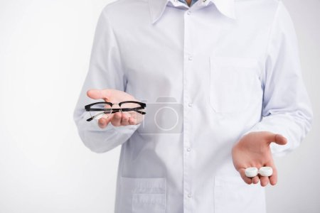 Photo pour Vue recadrée du médecin montrant sur les paumes lunettes et lentilles récipient, tout en choisissant des lunettes isolées sur blanc - image libre de droit