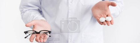 Cropped view of doctor holding on palms lenses container higher than eyeglasses isolated on white, banner