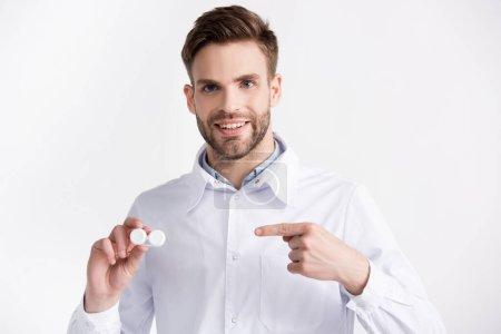 Photo pour Vue de face du médecin souriant pointant du doigt le récipient de lentilles, tout en regardant la caméra isolée sur blanc - image libre de droit