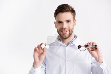 Front view of positive ophthalmologist with hands in air, showing eyeglasses and lenses container isolated on white