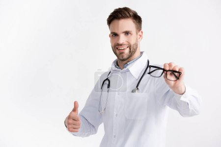 Photo for Smiling ophthalmologist with stethoscope, showing approval gesture, while showing eyeglasses on blurred foreground isolated on white - Royalty Free Image