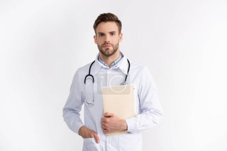 Front view of confident doctor with hand in pocket holding folder, while looking at camera isolated on white