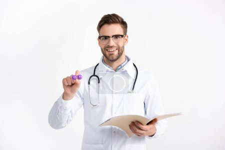 Front view of smiling doctor with folder showing lenses container isolated on white