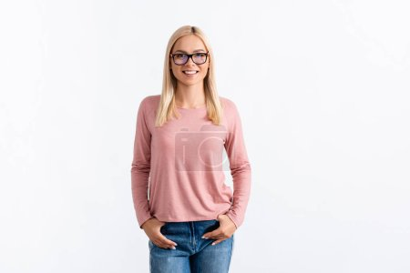 Front view of happy blonde woman with hands in pockets, wearing eyeglasses and looking at camera isolated on white