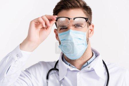 Photo pour Portrait de médecin avec masque médical regardant des lunettes à la vapeur isolées sur blanc - image libre de droit
