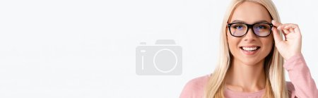 Portrait of happy blonde woman holding eyeglasses frame, while looking at camera isolated on white, banner