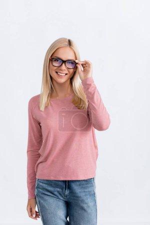 Photo pour Femme blonde souriante en jeans et rose à manches longues tenant cadre de lunettes, tout en regardant la caméra isolée sur blanc - image libre de droit