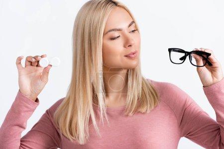 Photo pour Femme blonde regardant des lunettes tout en tenant des lentilles de contact isolées sur blanc - image libre de droit