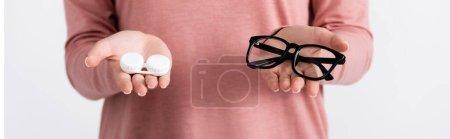 Photo pour Vue recadrée de la jeune femme tenant boîte avec des contacts et des lunettes isolées sur gris, bannière - image libre de droit