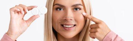 Photo pour Femme souriante pointant du doigt tout en tenant le récipient avec des lentilles de contact isolées sur blanc, bannière - image libre de droit
