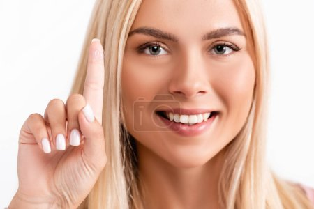 Smiling blonde woman holding contact lens and looking at camera isolated on white