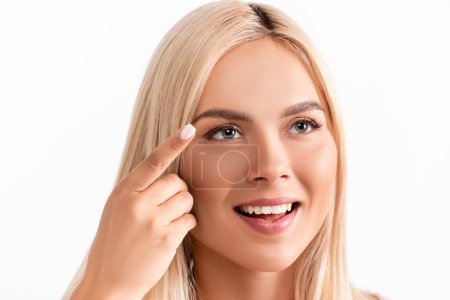 Positive blonde woman holding contact lens isolated on white