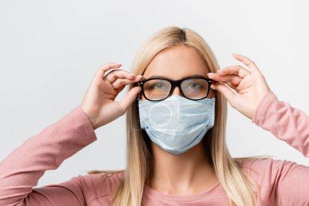 Photo pour Jeune femme au masque médical tenant des lunettes brumeuses isolées sur gris - image libre de droit