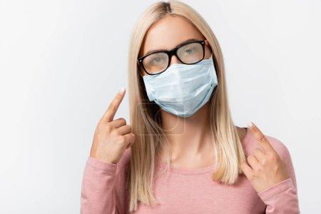 Photo pour Jeune femme au masque médical pointant du doigt des lunettes brumeuses isolées sur gris - image libre de droit