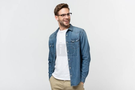Photo for Smiling man in eyeglasses with hands in pockets of pants looking away isolated on grey - Royalty Free Image