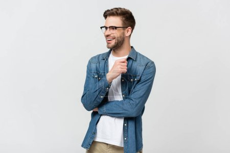 Cheerful man in denim shirt and eyeglasses looking away isolated on grey