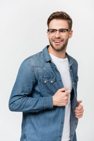 Photo for Young man in eyeglasses smiling while touching denim shirt isolated on grey - Royalty Free Image