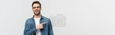 Smiling man in eyeglasses pointing with finger away isolated on grey, banner