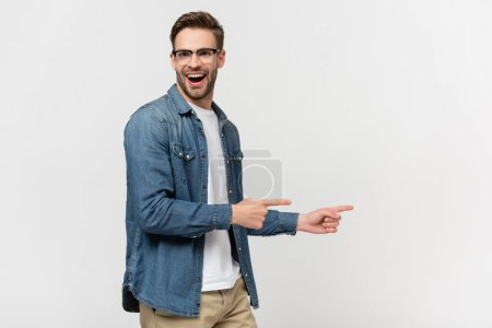 Cheerful man in eyeglasses pointing with fingers isolated on grey
