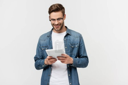 Photo for Smiling man in eyeglasses holding digital tablet isolated on grey - Royalty Free Image