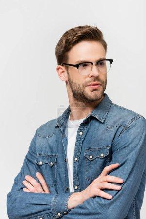 Hombre con gafas y camisa vaquera mirando hacia otro lado aislado en gris