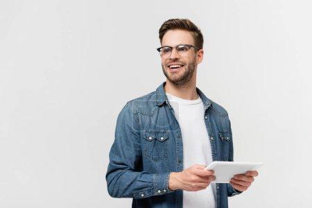 Hombre sonriente con gafas que sostiene la tableta digital aislada en gris
