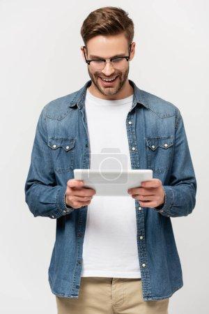 Photo pour Homme positif à lunettes utilisant une tablette numérique isolée sur gris - image libre de droit