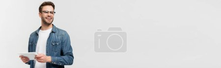 Photo for Young man in eyeglasses smiling and holding digital tablet isolated on grey, banner - Royalty Free Image