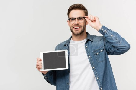Photo for Positive man touching eyeglasses while holding digital tablet with blank screen isolated on grey - Royalty Free Image